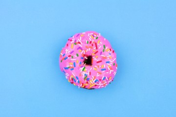 Single donut with pastel pink icing and sprinkles against a soft blue background. Minimal concept.