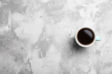 Ceramic cup with hot aromatic coffee on grunge background, top view