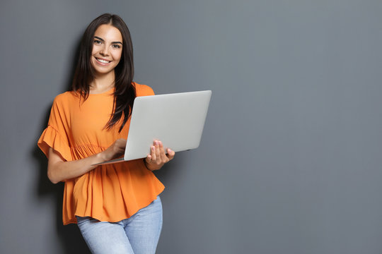 Young woman with modern laptop on grey background