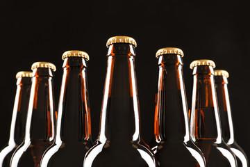 Many bottles of beer on dark background