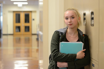 High School student in hallway with notebook