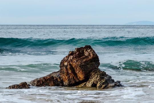 Wave cresting behind rock near the beach of Crystal Cove State Park in Laguna Beach, California. Foam from an earlier wave is in the foreground; Pacific ocean is in the background.