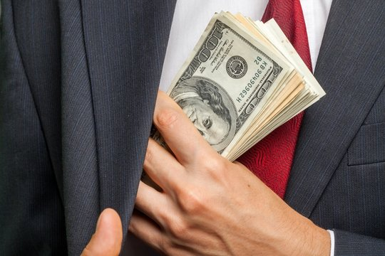 Closeup of a Businessman Putting Money in his Pocket