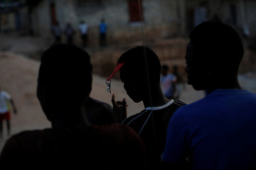 A key is seen hanging from a comb stuck in a boy's hair as he watches a football match in Port-au-Prince