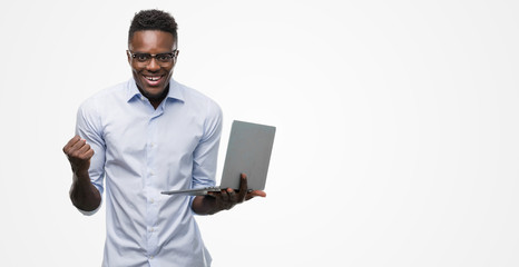 Young african american businessman using computer laptop screaming proud and celebrating victory and success very excited, cheering emotion