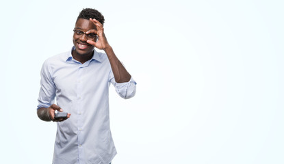Young african american man using smartphone with happy face smiling doing ok sign with hand on eye looking through fingers