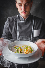 Cook chef holding creme soup with herbs, mushrooms, scallops and toast bred - added dried ice for smoking effect.