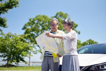 地図を見ながらドライブの行き先を話し合うシニアカップル
