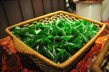 Green coconut candy wrapped in plastic for sale in a basket-Malaysian made candies