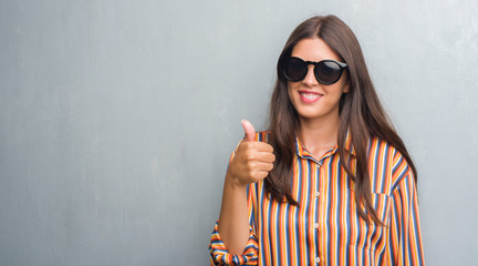 Young brunette woman over grunge grey wall wearing big sunglasses happy with big smile doing ok sign, thumb up with fingers, excellent sign