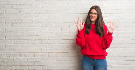 Young brunette woman standing over white brick wall showing and pointing up with fingers number ten while smiling confident and happy.