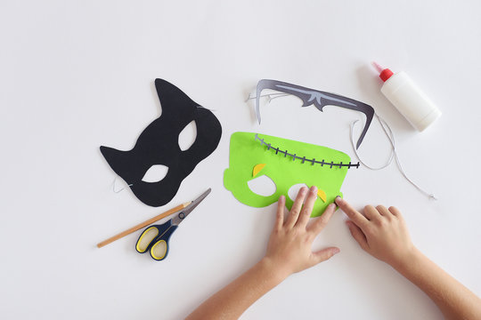 Making masks  paper  holiday Halloween Monster's  mask Black cat  Hands top view