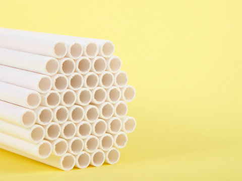 Dozens of biodegradable eco-friendly paper straws bundled together facing forward on a yellow background with copy space. Many cities are now banning single use plastic straws.