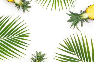 Frame of pineapple fruits and palm leaves on white background. Flat lay, top view. Tropical concept.