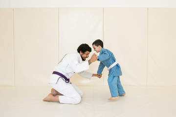 Father and little kid son are engaged in wrestling jiu-jitsu in the gym in a kimono. Trainer teaches child the methods and positions of single combat, karate or aikido.