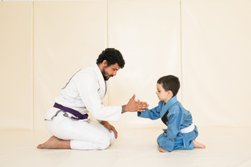Deurstickers Vechtsport Father and little kid son are engaged in wrestling jiu-jitsu in the gym in a kimono. Trainer teaches child the methods and positions of single combat, karate or aikido. Sport and healthy in family
