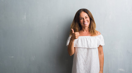 Middle age hispanic woman standing over grey grunge wall doing happy thumbs up gesture with hand. Approving expression looking at the camera with showing success.