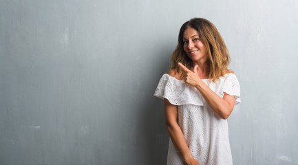 Middle age hispanic woman standing over grey grunge wall cheerful with a smile of face pointing with hand and finger up to the side with happy and natural expression on face looking at the camera.