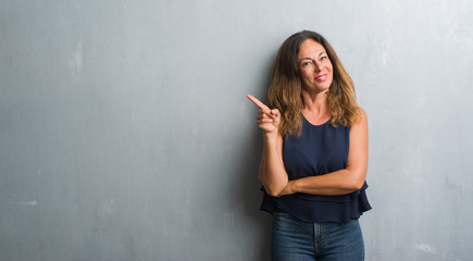 Middle age hispanic woman standing over grey grunge wall with a big smile on face, pointing with hand and finger to the side looking at the camera.