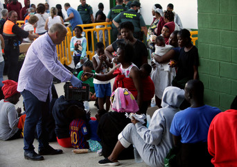 """Los Barrios' Major Jorge Romero, serves apples during a food distribution to migrants as they are guarded by Spanish Civil Guards at the """"Antonio Gavira"""" sports center after in Los Barrios"""