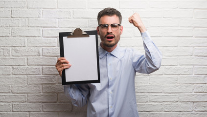 Young adult business man over brick wall holding clipboard annoyed and frustrated shouting with anger, crazy and yelling with raised hand, anger concept