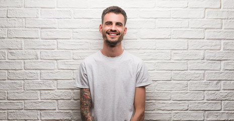 Young adult man standing over white brick wall with a happy face standing and smiling with a confident smile showing teeth