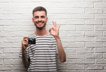 Young man holding vintage camera standing over white brick wall doing ok sign with fingers, excellent symbol
