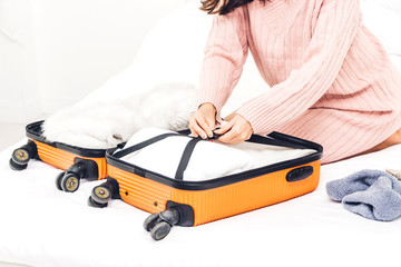 Woman packing a suitcase luggage and backpack for travel at home.Holiday vacation concept