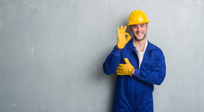 Young caucasian man over grey grunge wall wearing contractor uniform and safety helmet doing ok sign with fingers, excellent symbol
