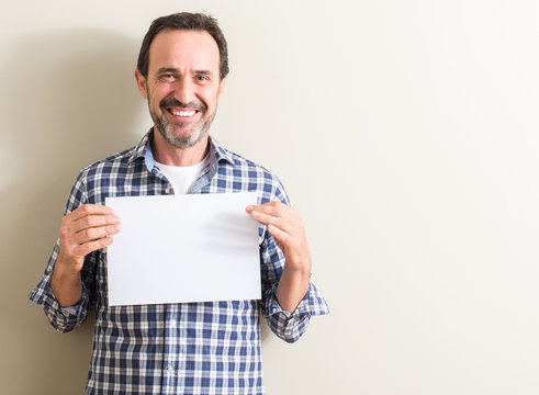 Senior man holding blank paper sheet with a happy face standing and smiling with a confident smile showing teeth