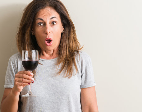 Middle age woman drinking red wine in a glass scared in shock with a surprise face, afraid and excited with fear expression