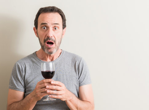Senior man drinking red wine in a glass scared in shock with a surprise face, afraid and excited with fear expression