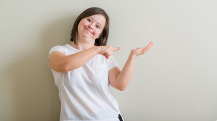 Down syndrome woman standing over wall amazed and smiling to the camera while presenting with hand and pointing with finger.