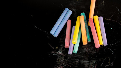 Multi color chalks on black background for copy space