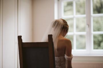 Mariée assise en face d'une fenêtre