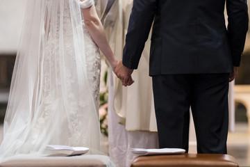 Mariés debout devant un prêtre