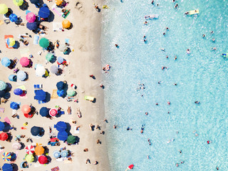 View from above, aerial view of an emerald and transparent Mediterranean sea with a white beach full of beach umbrellas and tourists who relax and swim. Costa Smeralda, Sardinia, Italy.