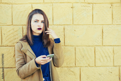 9494afa3d9 Cute young woman meeting during mobile conversation standing outdoors on  yellow promotional background for advertising. Smiling young student  blogger ...