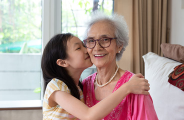 Portrait of cute little girl and her beautiful grandma sitting on sofa at home ,Asian girl kissing her smiling granny in cheek