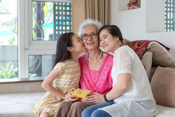 Beautiful senior woman is sitting with gift box and smiling while her daughter and granddaughter are kissing her in cheeks on sofa at home