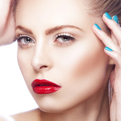 Close-up beauty girl face with bright make-up, red lips, blue eyes, clean skin, hand near hair with nail polish manicure