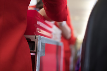 flight attendant serving food to passenger on aircraft. stewardess offer drink on board. hostess with trolley