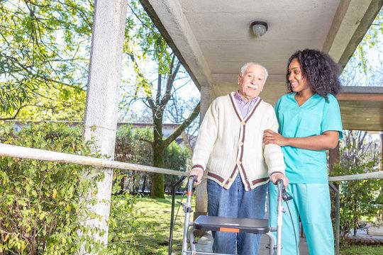 African nurse helping elderly man with walker in rehab facility hallway
