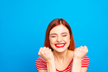 Portrait of nice vivid girlish red straight-haired happy smiling toothy young girl celebrating lottery victory winning, closed eyes, isolated over blue background