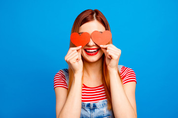 I love you! Close up studio photo portrait of cute lovely pretty with beaming toothy smile girl covering eyes with small little postcards in shape on heart isolated bright vivid background
