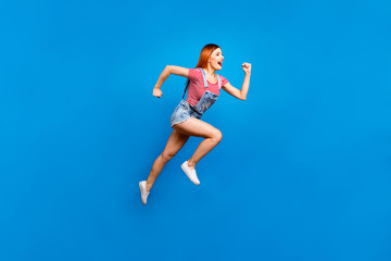 Full-size portrait of running marathon girl who looks in front of her isolated on bright blue background