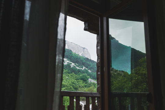 Mountain view through open window on balcony, rocks in cloudy and foggy weather