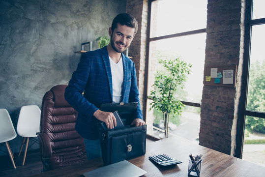 Attractive handsome young brunet bearded executive worker smiling cheerful man, accountant at workstation workplace. Finishing, collecting things in breif-case after work day goes home