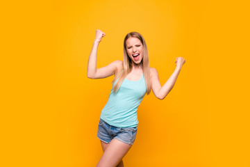 Yes, they did it! Happy blond girl raises her hands in fist isolated on vivid yellow background with copy space for text