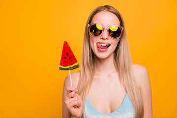 Attractive nice cute childish straight-haired beautiful blonde girl, wearing blue swimsuit, color sun glasses, fooling, showing tongue out, holding candy on stick. Isolated over yellow background
